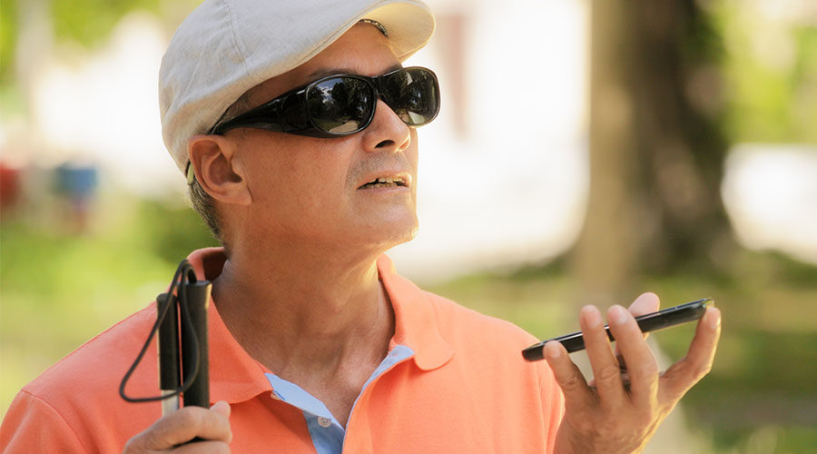 A man with a visual impairment uses a cell phone outside.
