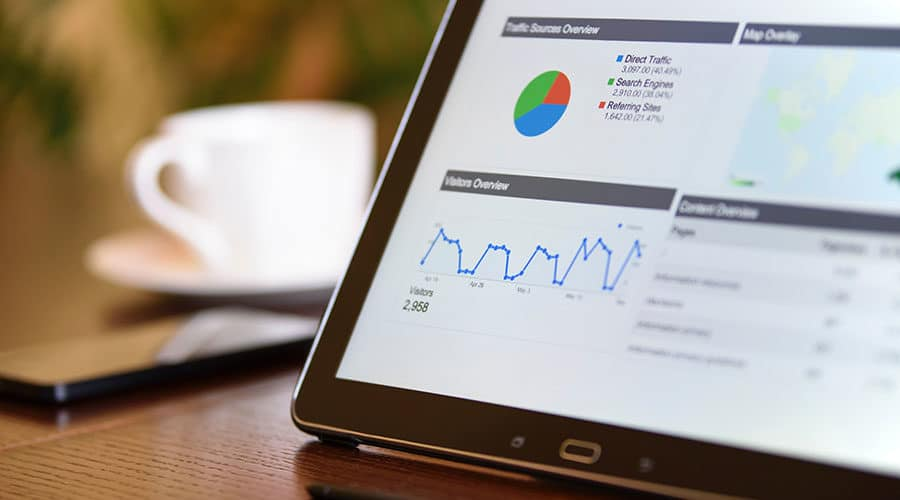 A tablet shows some basic website analytics charts in the foreground. A cell phone and a white teacup and saucer in the background.